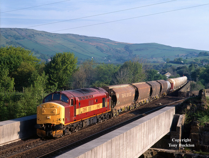 37695 crosses the A6 at Chapel-en-le-Frith, with the 6H99 04:38 Warrington Arpley - Dowlow, at 07:38 on the Morning of May 16th 2002. The consist was significantly boosted by the addition of cement tanks to be set down at Peak Forrest on this day.