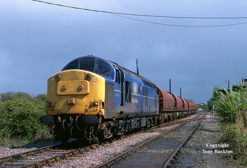 A scruffy looking 37047 waits to depart from the EWS train office, Hull King George Dock, with the 6D54 Enterprise to Doncaster at 13:40 on 1st May 2003 following a heavy rain storm.
