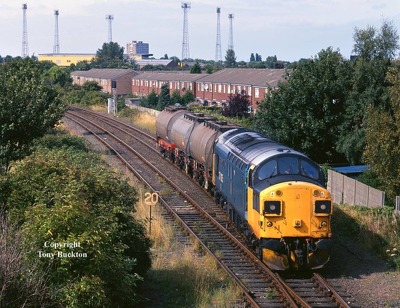 """37025 'Inverness TMD' in somewhat patchy remains of BR Large Logo blue made for an interesting visitor to Hull on August Bank Holiday Monday (31st) 1998. Photographed on the approach to Hessle Road Junction with the 6D54 13:56 Enterprise service to Doncaster formed of just 3 Acitic Acid tanks from Saltend destined for Spondon near Derby. These tanks would normally run as 6M88 direct to Spondon during this period, however,I can only surmise that a pause at Doncaster must have been required on this day, possibly due to the Bank Holiday.<br /> As the consist followed a stopper, a quick dash back to my car and a chase to Lowfield Lane was on;<br /> <a href=""""https://tonybuckton.smugmug.com/Trains/Class-37s-through-the-ages/i-J5kF5ZC"""">https://tonybuckton.smugmug.com/Trains/Class-37s-through-the-ages/i-J5kF5ZC</a>"""