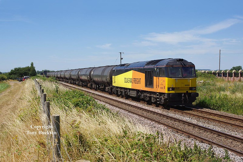 60095 approaches Stainforth on the line from Skellow Jnc as the train crosses Stainforth Road, Barnby Dun, at 12:58 on Monday 2nd July 2018, with the 08:55 Colas Ribble Rail (Preston) - Lindsey Oil Refinery empty tanks.