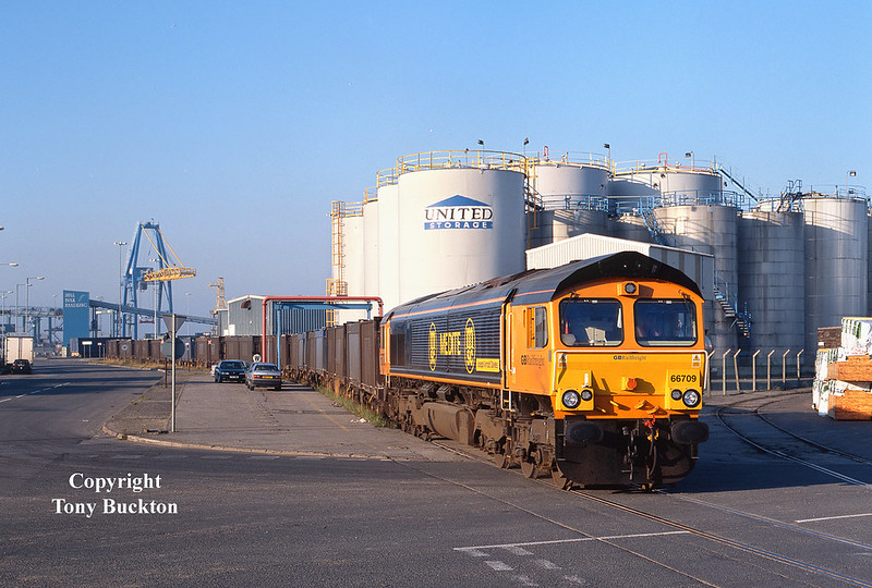 The sporadic Importing of Gypsum through Hull King George Dock began in 2002 when the recently founded GBRailfreight won the initial short term contract.  Looking resplendent in the morning sunshine, 66709 'Joseph Arnold Davies' runs along the Eastern access road shortly after departure from 10 Quay, with the 4Z50 07:40 to Kirkby Thore on Wednesday 11th September 2002.