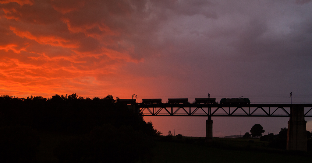 Sunset between two thunderstorms as a limestone train heads out onto the Viaduc de Moresnet bound for Aachen-West.