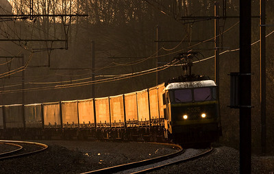 2025 brings an Ambrogio intermodal train east out of the setting sun at Remersdaal.