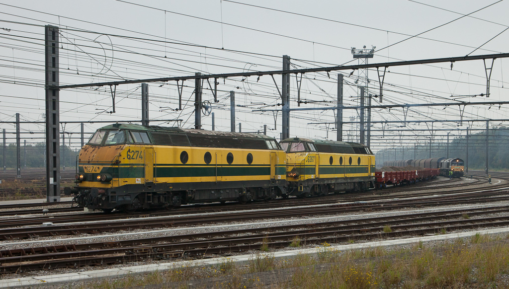 6274+6267 on ballast train duty pass Railtraxx 266 118 with the Voest-Alpine steel train Linz/A - Antwerpen in Montzen. The main was out of service for switch replacements and all trains detoured through the yard in mid-October 2015.