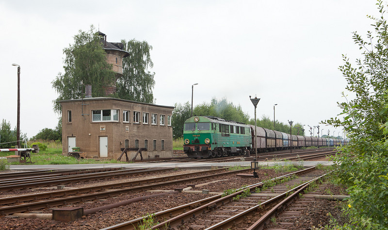 PKP SU46-046 passes tower W1 and an ancient water tower departing Horka Gbf eastbound with an empty coke train.