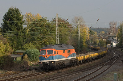 Nordbayrische Eisenbahn 232 105 heads westbound under threatening skies with a ballast train in Eschweiler. This engine arguably wears the weirdest paint scheme on rails today. Ehf tower is visible in the background, still manned.