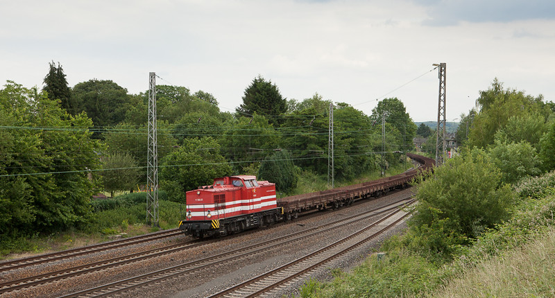 Hessische Gueterbahn V100.01 with a train of low-side gondolas in Eschweiler.