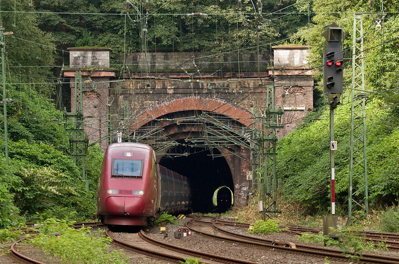 Nestled deep in the forest south of Aachen lay the original 1850s Busch Tunnel. In 2004 it was still in use in mostly its original form, but big changes were a-coming. Today this scene has changed completely, with the new tunnel having consumed the hillside to the left.<br /> <br /> That's an ICE exiting the south portal visible in the distance while this Thalys enters the old Aachen Süd yard on its run to Köln.