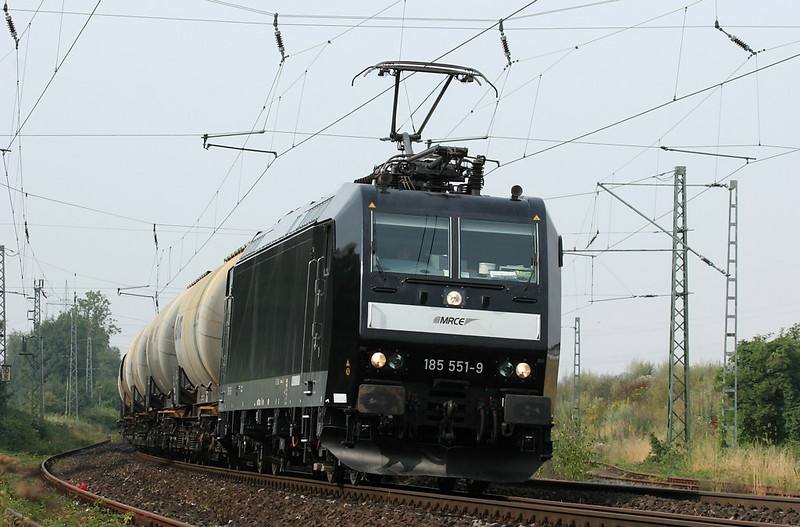 Soda ash is an ingredient used in glass making. This empty train returns from the Vegla glass plant in Stolberg to eastern Germany for a fresh load. Squeaky clean MRCE 185 551 (operating under lease to Veolia) powers it northbound through Kohlscheid.