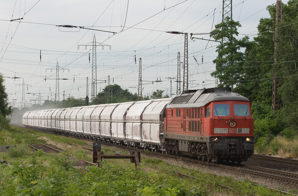 Lintorf sits just north of the junction with the Angertalbahn, a branch line running to a large limestone quarrying operation at Flandersbach. Several trains daily ply that line carrying lime to the blast furnaces in the Ruhr area and the Netherlands. Here 232 575 is seen returning with a Dutch empty train, trailing a nice dust cloud on a hot and muggy day in 2008.  If you pass through the Duisburg-Düsseldorf area and want to stop over and railfan for a couple hours, this place is excellent. You can drive right up to it and sit in your car while you wait. A nearby grade crossing as well as signals alert you to oncoming trains. There is usually a lot of traffic through Lintorf on any given day except Sundays and Mondays.