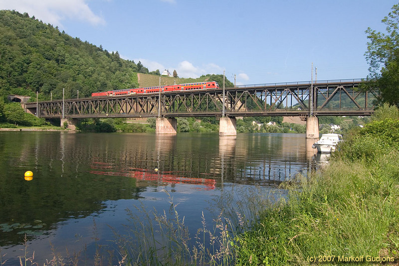 A push-pull set of double deck cars crosses the Mosel River at Bullay. The bridge is a bilevel design with a road on the lower level.