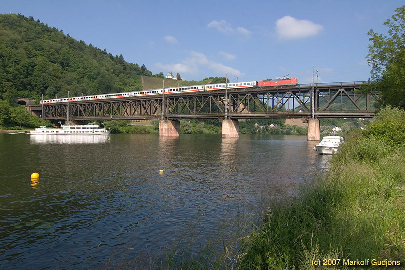 A class 181.2 with an Intercity train en route from Luxembourg to Koblenz is greeted by a ship on the Mosel River.