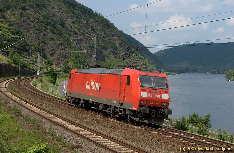 185 180-7 is representative of modern AC traction power that is quickly replacing the first post-war standardized electric engines. Running light engine downriver it passes Kattenes.
