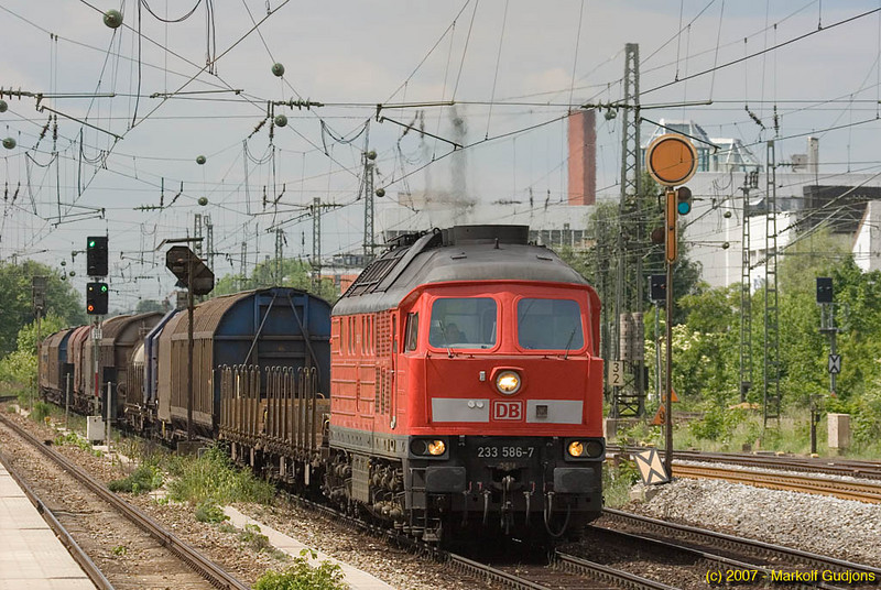 "A russian-buit class 233 ""Ludmilla"" roars past the passenger platforms at the Heimeranplatz with her eastbound mixed freight."