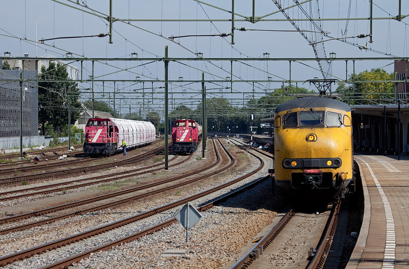 Sittard is the center of freight activity in Dutch Limburg. Here Railion-NL 6512 has backed against the empty limestone train  49665 (Beverwijk - Hermalle/B) while 6518 is preparing to take an extra tankcar train south into Belgium. The Plan V on the right has completed its station stop and is accelerating towards Maastricht.