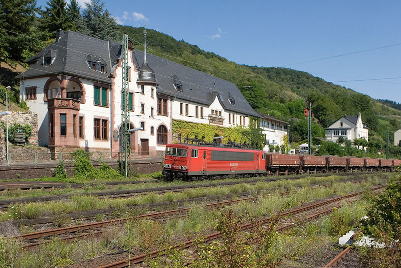 "DB is notorious for minimizing the use of vegetation control chemicals, leading to scenes like this. A former ex-GDR class 155 electric leads a train of Difco ballast cars northbound through a sea of green at Lorch. In some parts of the country the situation is so bad that engines act as ""lawn mowers""."