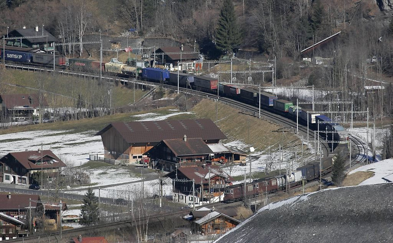 Doubleheaded Re 4/4s lead a train downhill through Blausee-Mitholz.
