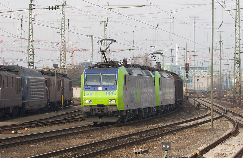 BLS 485 006 and a sister bring a unit train of boxcars through Basel Bad Bf en route to Switzerland. The stark green class 485s are a hallmark of BLS Cargo. The Re 465 and Re 4/4 Is parked on the left are also owned by BLS.