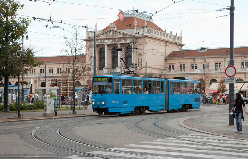 A pedestrian yields to Tatra KT4YU 330 on line 9 in front of the main station as the streetcars tend not to stop at crossings.