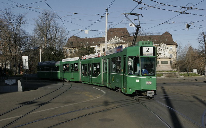 Basel - a six-axle articulated car pulling an old four-axle trailer swings onto the Centralbahnplatz, preparing to stop.