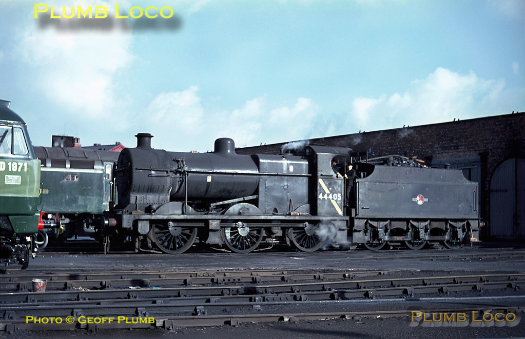 LMS 4F 0-6-0 No. 44405 is another of the works pilots at Crewe Works, here standing outside the old Paint Shop between bouts of shunting. It is carrying a BR standard chimney in place of its original LMS type and also has the yellow diagonal stripe on the cabside, denoting it is not allowed to work under the electrification wires south of Crewe. Tuesday 2nd November 1965. Slide No. 1670.