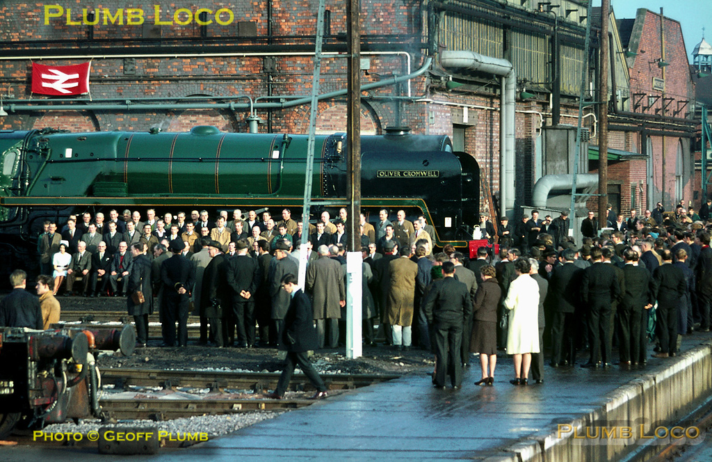 "From the Geoff Plumb Collection of original slides. On Friday 3rd February 1967 a ceremony was held at Crewe Works to mark the final steam overhaul when BR ""Britannia"" class 4-6-2 No. 70013 ""Oliver Cromwell"" was outshopped in fully lined BR greeen livery. Many of the staff involved are lined up in front of the loco for a photocall, watched by other staff and invited guests, with the engine posed in steam outside the erecting shop facing on to the traverser.  Photographer unknown. Collect Slide No. 2676."