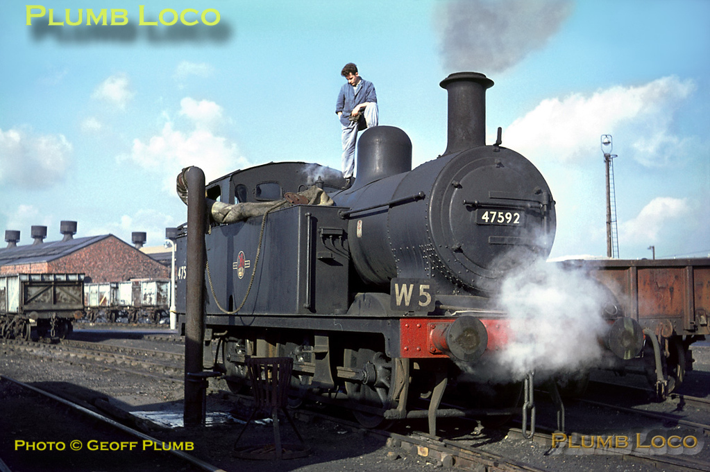 """LMS """"Jinty"""" class 3F 0-6-0T No. 47592 is one of the works pilots at Crewe Works, carrying duty board W5. The fireman watches the water level in the tanks as the loco is serviced near to the old Paint Shop area in the works on Tuesday 2nd November 1965. Slide No. 1668."""
