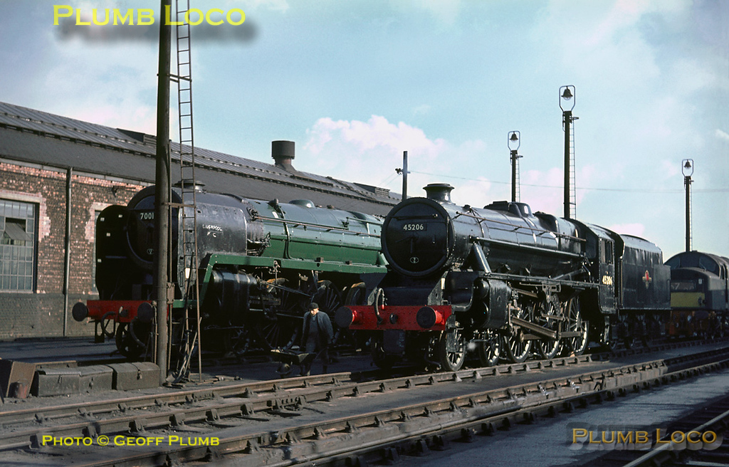 """BR Standard """"Britannia"""" Class 4-6-2 No. 70016 """"Ariel"""" and """"Black 5"""" 4-6-0 No. 45206 have recently been outshopped and are standing on the steam test roads near the old Paint Shop. Both have been repainted, but only in unlined green and black respectively. 70016 has had its nameplate removed and someone has scrawled """"Liverpool FC"""" on the smoke deflectors! An English Electric Type 4 diesel (Class 40) just manages to get its nose into the picture. Tuesday 2nd November 1965. Slide No. 1672."""