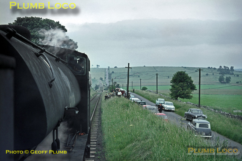 """From the footplate of 68012, fellow J94 68079 is seen leading gingerly down the 1 in 14 gradient of Hopton Incline with the RCTS """"High Peak Railtour"""" of Saturday 27th June 1964, plenty of roadborne photographers having arrived in some interesting contemporary cars! Slide No. 746."""