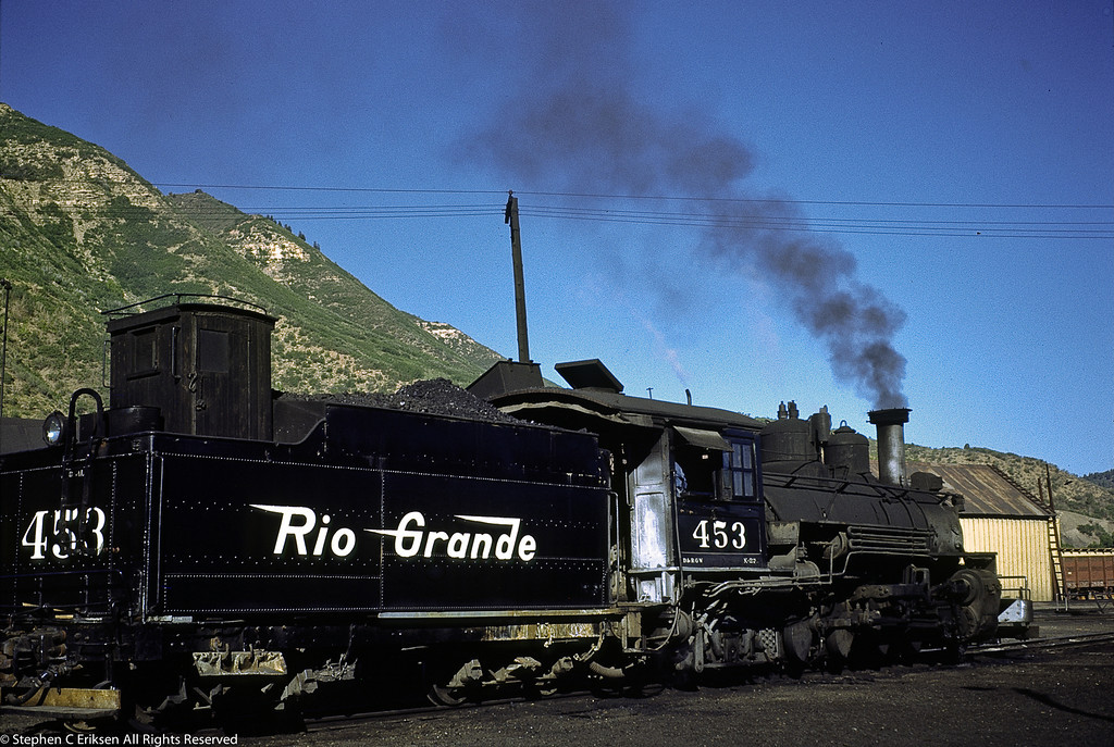 A beautiful shot of K-27 #453 in the yards of Durango adjacent to the car shop in June of 1951.  Note the doghouse on the tender and the footboards to aid in switching duties.