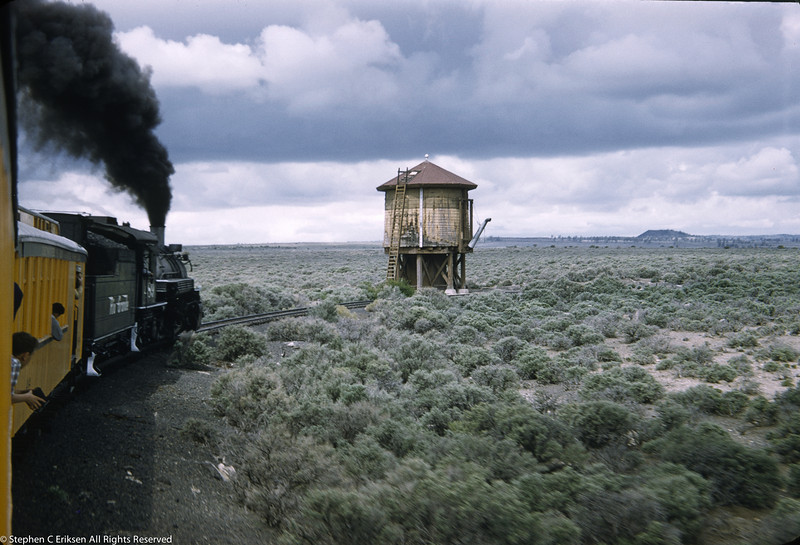 K-36 #489 approaches a welcome water tower in a desolate 1957 landscape.