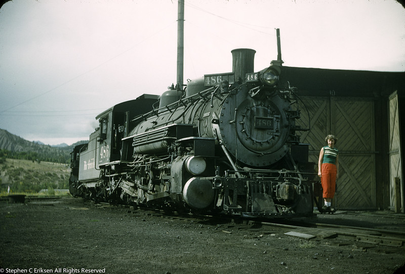 In this 1950's view, K-36 #486 serves as a backdrop for a young lady to have her picture taken in the Durango yard.