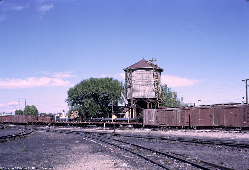 Wooden rolling stock repose next to the Alamosa water tower, September 1966.