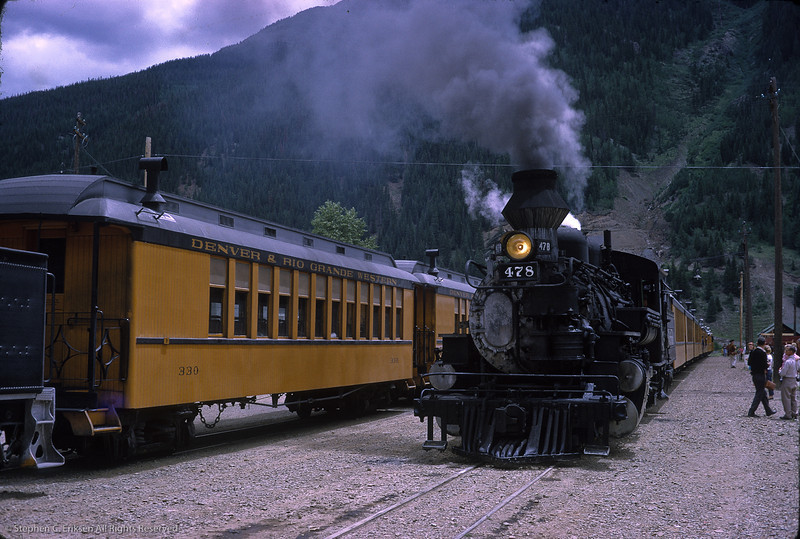 Two trains are present in Silverton in this classic view on July 16th, 1965.  Note the steel coach #330 produced by the Burnham shops for the Silverton train.