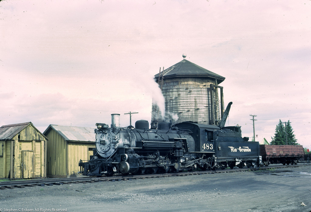 K-36 #483 pauses in front of the water tower in June of 1966 with just a single drop bottom gondola in tow.