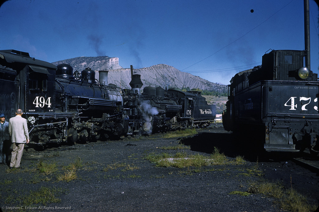 A busy September day in 1961 at the Durango facilities! K-28 #476 and K-37 #494 meet head to head while #473 simmers on an adjacent track.