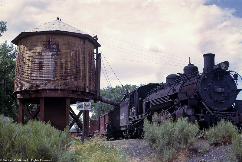 Former standard gauge engine #498 takes on water in the view from July of 1963.