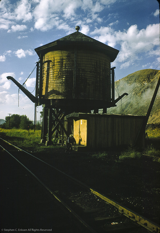 A worker in his cowboy hat rests beside the Durango water tower.  The second spout was added for a movie. Photo taken in September of 1961.