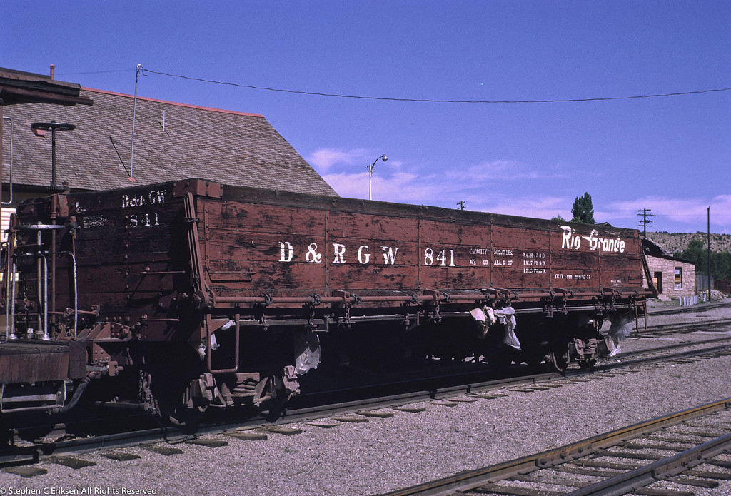 Drop bottom gondola number 841 sits connected to caboose 0540 in front of the Durango station in July 1970