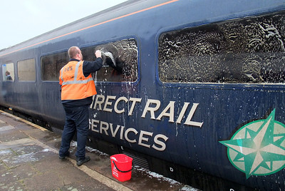 Driver Tony Kay gets to grips with window cleaning in the platform at Workington, 22/01/10.