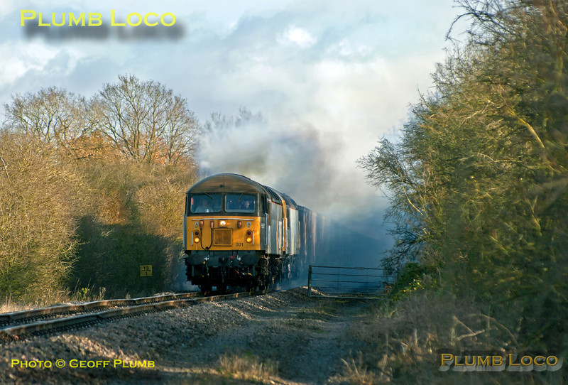 56301 is now leading with failed 56312 behind, but both locos producing voluminous clouds of smoke, as the train approaches Charndon having departed from Claydon L&NE Junction at 11:27, a few minutes earlier than the booked time. It was though 24 hours late as 56312 failed the day before, having got as far as Claydon with 6Z91, the 10:55 fly ash empties from Calvert to Didcot Power Station. 11:28, Tuesday 4th December 2012. Photo taken from a public footpath across the line. Digital Image No. GMPI13101.