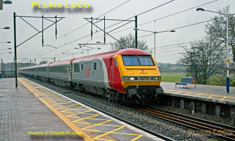"""In miserable light and pouring rain, the unusual sight of the """"Pretendolino"""" set on the East Coast Main Line as it passes northbound through Brookmans Park station. This was 1Z90, 14:21 from King's Cross to Wakefield Westgate, a football charter train for Chelsea fans. DVT 82126 is leading with 90044 on the rear. 14:40, Wednesday 19th December 2012. Digital Image No. GMPI13285."""