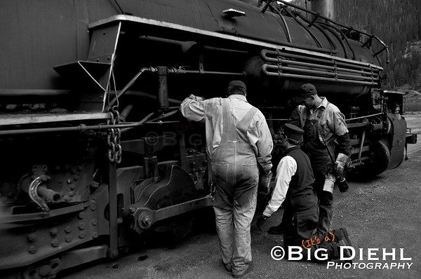 Preparing for the final departure from Silverton, the Engineer, Fireman, and one of the train's brakemen look over a part before pulling out.