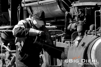 The mechanical nature of steam railroading requires lots of lubrication due to the metal on metal surfaces.  While loading the passengers here on 12th Street, the fireman, is oiling around the locomotive on every surface that needs it.