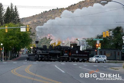 Durango & Silverton K-28 #478 makes an appearance as its former self, #478 of the Denver and Rio Grande Western.  Here the train crosses over the intersection of Main Avenue, 14th Street, and Camino del Rio.  This shot, is the opposite of the opening scenes of this video from 2010, seen here.