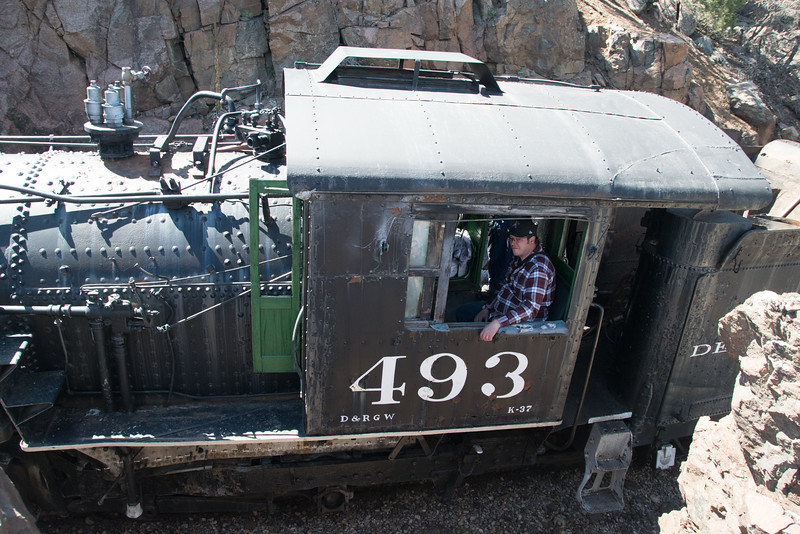 """K37 Locomotive 493 (inoperable) was brought from the Silverton yard to the Durango yard on May 4, 2016. This photo was taken along the famous """"Highline"""". Paul C sits in the fireman seat (no fire)."""