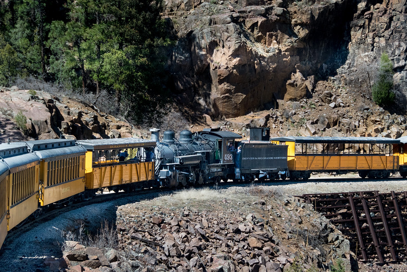 """K37 Locomotive 493 (inoperable) was brought from the Silverton yard to the Durango yard on May 4, 2016. This photo was taken along the famous """"Highline"""". Cars were needed on both sides of the locomotive to provide braking power in the air system."""