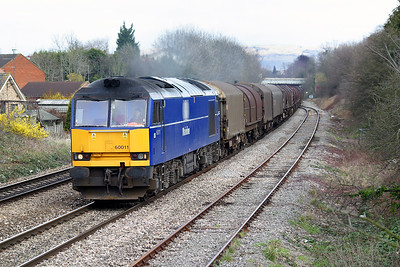 On Cheltenham Gold Cup day, 60011 in Mainline blue livery passes Hatherley Loop, Cheltenham with 6V05 09.55 Round Oak to Margam empty covered steel carriers. 13th March 2003.