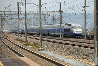 A pair og Duplex TGV's arrive eastbound at Avignon TGV Station. The leading unit 611 carries the inscription on the nose ' 100th Duplex built'. To the right of the power car, the high speed line can be seen climbing steeply on the viaduct over the Rhone Valley. 04/06/2011