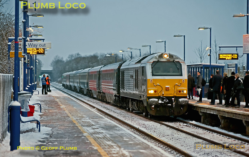 "There was a moderate snowfall on the previous night and just enough light to get a shot at Haddenham station as 67015 ""David J. Lloyd"" arrives with 1H08, the 06:53 from Banbury to Marylebone. The seven coach set eases into the station at 07:19, watched by the passengers and snow clearance team on the platform. Friday 10th February 2012. Digital Image No. GMPI10953."